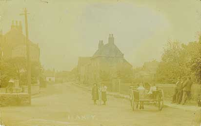 Early postcard of Low Street and the Market Cross